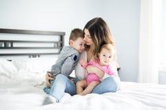 Счастливая мать семьи и 2 дет, сын и дочь в кровати Стоковое фото RF