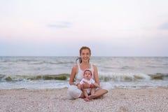 Счастливая мать семьи и дочь ребенка делая йогу, размышляют в положении лотоса на пляже на заходе солнца Стоковое Фото