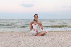 Счастливая мать семьи и дочь ребенка делая йогу, размышляют в положении лотоса на пляже на заходе солнца Стоковая Фотография RF