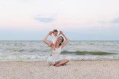 Счастливая мать семьи и дочь ребенка делая йогу, размышляют в положении лотоса на пляже на заходе солнца Стоковое фото RF