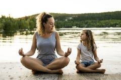 Счастливая мать семьи и дочь ребенка делая йогу стоковая фотография rf