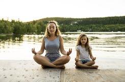 Счастливая мать семьи и дочь ребенка делая йогу стоковое изображение rf