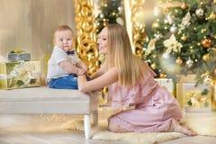 Счастливая мать семьи и сын младенца маленький играя домой на праздниках рождества Малыш с мамой в festively украшенной комнате с стоковое фото
