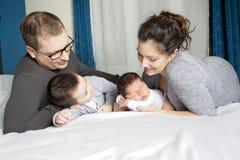 Счастливая мать семьи, отец и 2 дет дома в кровати Стоковое Изображение