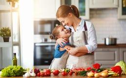 Счастливая мать семьи с девушкой ребенка подготавливая салат овоща стоковая фотография rf