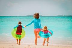 Счастливая мать с бегом сына и дочери имеет потеху на пляже Стоковое Фото