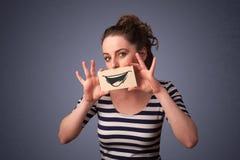 Счастливая милая девушка держа бумажной с смешным чертежом smiley Стоковые Фото