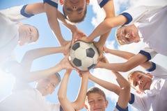 Счастливая младшая футбольная команда держа шарик Стоковое Изображение