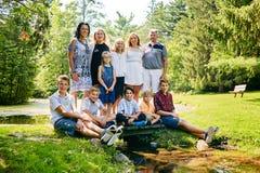 Счастливая многодетная семья представляя в сценарном парке лета Стоковые Изображения RF