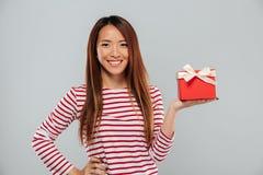 Счастливая молодая азиатская дама держа подарок стоковая фотография rf