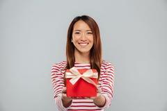 Счастливая молодая азиатская дама держа подарок стоковые фото