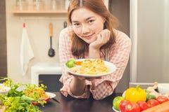 Счастливая молодая азиатская женщина гордо показывая ее варя блюдо, макаронные изделия Стоковые Фото