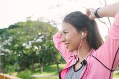 Счастливая молодая азиатская женщина нагревая ее тело путем протягивать ее тело перед тренировкой утра и йогу в парке Стоковые Фотографии RF