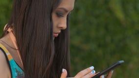 Счастливая молодая азиатская женщина при smartphone стоя в улице сток-видео