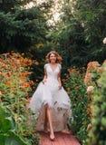 Счастливая молодая белокурая девушка в элегантном изумительном длинном белом платье света свадьбы с длинным поездом, идя в чудесн стоковое фото rf