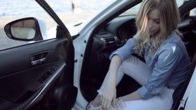Счастливая молодая белокурая женщина сидя в белом автомобиле акции видеоматериалы