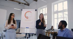 Счастливая молодая белокурая финансовая женщина тренера дела уча многонациональным работникам объединяется в команду на современн акции видеоматериалы