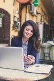 Счастливая молодая бизнес-леди работая на кафе, используя мобильный телефон Стоковая Фотография RF