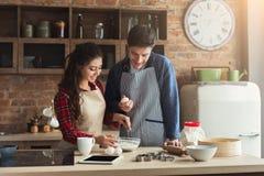 Счастливая молодая выпечка пар в кухне просторной квартиры стоковое изображение