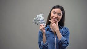 Счастливая молодая дама держа банкноты доллара, думающ о покупках или каникулах сток-видео