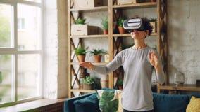 Счастливая молодая дама носит искусственные стекла реальности стоя дома в квартире и показывать стиля просторной квартиры курчаво видеоматериал