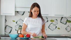 Счастливая молодая домохозяйка режа свежий огурец в уютной кухне видеоматериал