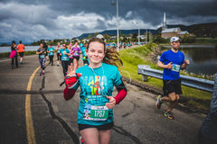 Счастливая молодая женщина бежать 10K и слушая некоторая музыка Стоковое фото RF