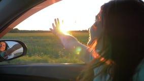 Счастливая молодая женщина в автомобиле и руке играя в воздухе на лучах захода солнца видеоматериал