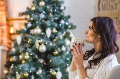 Счастливая молодая женщина в белый связанный носить с чашкой кофе или чаем дома стоковое фото rf