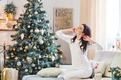 Счастливая молодая женщина в белый связанный протягивать свитера стоковые изображения rf