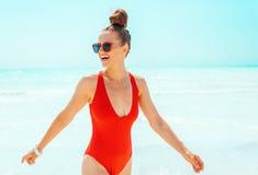 Счастливая молодая женщина в красном swimwear на пляже имея время потехи стоковое фото