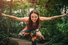 Счастливая молодая женщина делая йогу работает для баланса на парнике Стоковое Фото