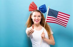 Счастливая молодая женщина держа американский флаг стоковые изображения