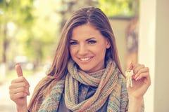 Счастливая молодая женщина держа ключи и показывая большие пальцы руки вверх стоковое изображение rf
