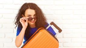 Счастливая молодая женщина держа оранжевый чемодан, идя на отключение Солнечные очки красивой девушки нося перед путешествовать О стоковое изображение rf