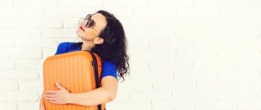 Счастливая молодая женщина держа оранжевый чемодан, идя на отключение Солнечные очки красивой девушки нося перед путешествовать О стоковые изображения