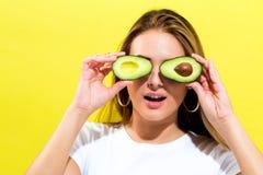 Счастливая молодая женщина держа половины авокадоа Стоковая Фотография RF