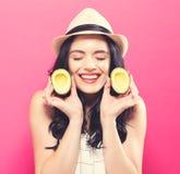 Счастливая молодая женщина держа половины авокадоа Стоковое Фото