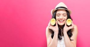 Счастливая молодая женщина держа половины авокадоа Стоковое Изображение RF