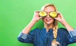 Счастливая молодая женщина держа половины авокадоа Стоковая Фотография