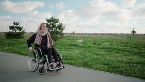Счастливая молодая женщина завихряет ее тело в кресло-коляске в районе парка в солнечном дне акции видеоматериалы