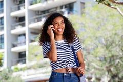 Счастливая молодая женщина идя и говоря на мобильном телефоне снаружи Стоковая Фотография