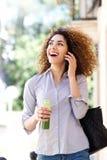 Счастливая молодая женщина идя и говоря на сотовом телефоне Стоковая Фотография