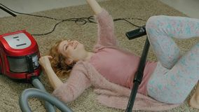 Счастливая молодая женщина или домохозяйка с пылесосом, лежа на поле, используя телефон, имеющ потеху, играя сток-видео