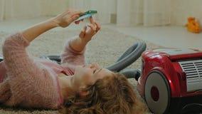Счастливая молодая женщина или домохозяйка с пылесосом, лежа на поле, используя телефон, имеющ потеху, играя акции видеоматериалы