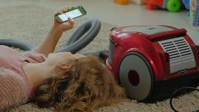 Счастливая молодая женщина или домохозяйка с пылесосом, лежа на поле, используя телефон, имеющ потеху, играя видеоматериал