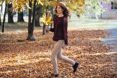 Счастливая молодая женщина имея время потехи в осени outdoors Жизнерадостная усмехаясь девушка скача бегущ осенью лес стоковые изображения
