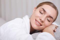 Счастливая молодая женщина лежа на таблице массажа стоковая фотография