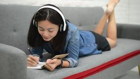 Счастливая молодая женщина лежа на чертеже софы что-то в блокноте и слушая музыке сток-видео