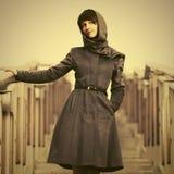 Счастливая молодая женщина моды в классическом пальто на шагах Стоковое Изображение
